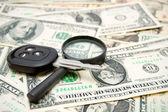 Keys from the car and a magnifier on money. — Stock Photo