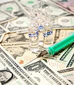 Syringe and ampoules on money. — Stock Photo