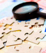Puzzle and magnifier on documents. — Stock Photo