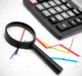 Magnifier and the calculator on graphs. — Stock Photo
