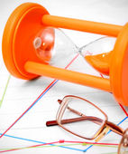 Sand-glass and glasses on graphs. — Stock Photo
