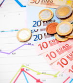 Coins and banknote euro on graphs. — Stock Photo