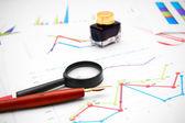 Caneta, tinta e uma lupa em gráficos. — Fotografia Stock