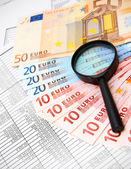 Magnifiers and denomination euro on documents. — Stock Photo