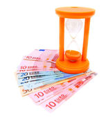 Sand-glass and euro banknotes. On white. — Stock Photo