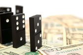 Dominoes on money (dollars). — Stock Photo