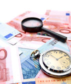 Magnifiers and watch on the money. — Stock Photo
