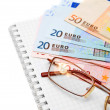 Stock Photo: Glasses and banknote euro on notebook.