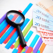 Stock Photo: Magnifier and banknote euro on graphs.