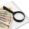 Magnifier and dollars on a notebook. — Stock Photo