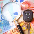 Stock Photo: Magnifier and key from car for euro banknotes.