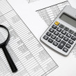 Magnifier and the calculator on documents. — Stock Photo