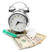 Compresse, una siringa e una sveglia sul denaro. — Foto Stock