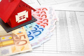 Toy house and money on the documents. — Stock Photo