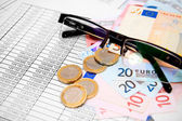 Glasses, euro and coins on documents. — Stock Photo