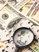 Lupa e quebra-cabeça em dólares. — Fotografia Stock