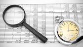 Lupa e relógio em documentos. — Fotografia Stock
