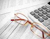 Glasses and the calculator on documents. — Stock Photo