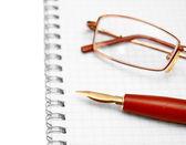 γυαλιά σε ένα σημειωματάριο και στυλό. — Φωτογραφία Αρχείου