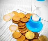 Coins and a sand-glass on documents. — Stock Photo