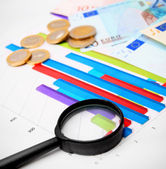 Magnifier and coins on graphs. — Stock Photo