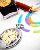 Watch and pen on graphs. — Stock Photo