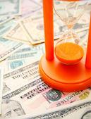 Sand-glass on dollars. — Stock Photo