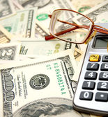 Glasses and the calculator on dollars. — Stock Photo
