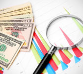 Magnifiers and money on graphs. — Stock Photo