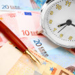 Pen and an alarm clock for euro banknotes. — Stock Photo