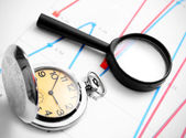 Magnifier and watch on graphs. — Stock Photo