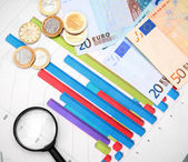 Magnifiers and euro money on graphs. — Stock Photo