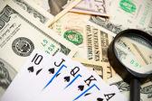 Cartões de jogo e lupa em dólares. — Fotografia Stock