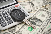 Key from car and the calculator on money. — Stock Photo