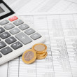 Calculator and coins on the documents — Stock Photo