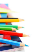 Multi-coloured pencils and writing-books on a white background. — Foto Stock