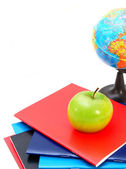 School. The globe, an apple and writing-books on a white background. — Stock Photo