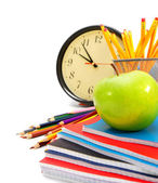 Back to school. Watch and an apple with writing-books on a white background. — Stock Photo
