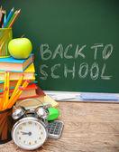Reloj con alarma y accesorios escolares contra una junta escolar. regreso a la escuela. — Foto de Stock