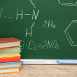 Pile of books against a school board with chemical formulas. — Stockfoto