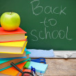 Books, an apple and school tools against a school board. Back to school. — Stock Photo