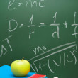 Apple and writing-books against a school board with mathematical formulas. — Stock Photo