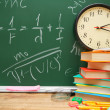 Watch and an apple with school accessories against a school board (mathematical formulas) — Stock Photo