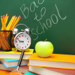 Back to school. An alarm clock, an apple and school accessories against a school board. — Stock Photo