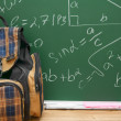 School bag against a school board with mathematical formulas. — Stock Photo #32460883