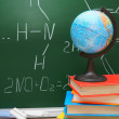 The globe and books against a school board (chemical formulas). — Stock Photo