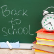 Alarm clock on books. Against a school board. Back to school. — Stock Photo