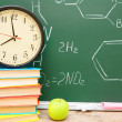 Stock Photo: Watch on books, and apple against school board (chemical formulas).
