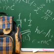 School bag against a school board (the formula on the physicist). — Stock Photo