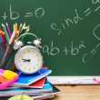 Apple, alarm clock and other school subjects against a school board (mathematical formulas). — Stock Photo